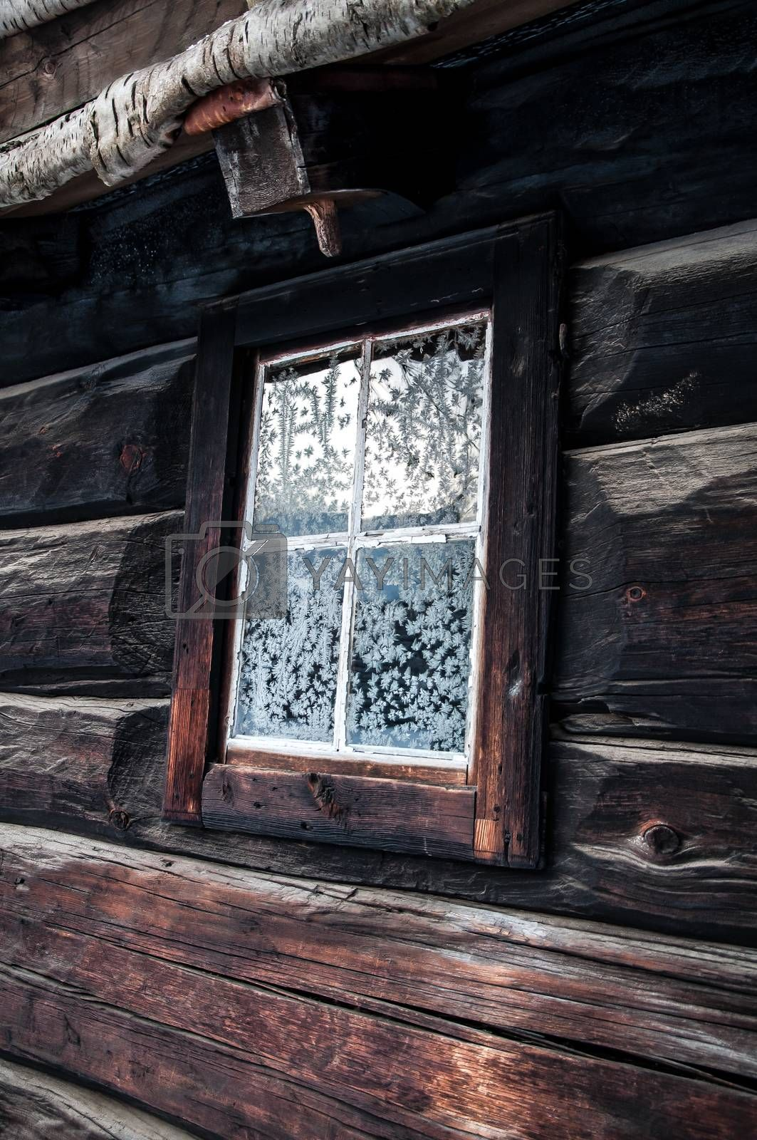 An old house in the winter with snowcrystals on the window.