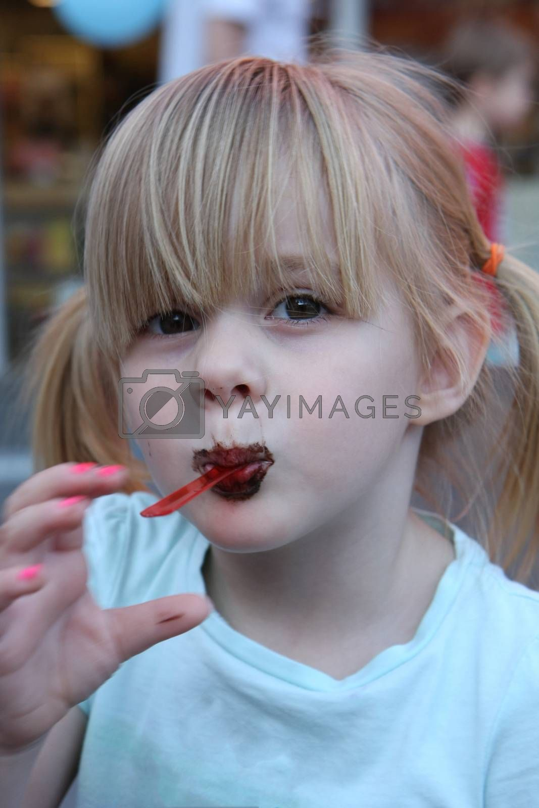 Little girl being silly while eating ice cream