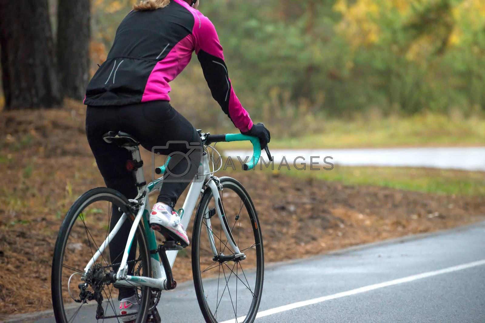 Young Woman in Pink Jacket Riding Road Bicycle in the Park in the Cold Autumn Day. Healthy Lifestyle. by maxpro