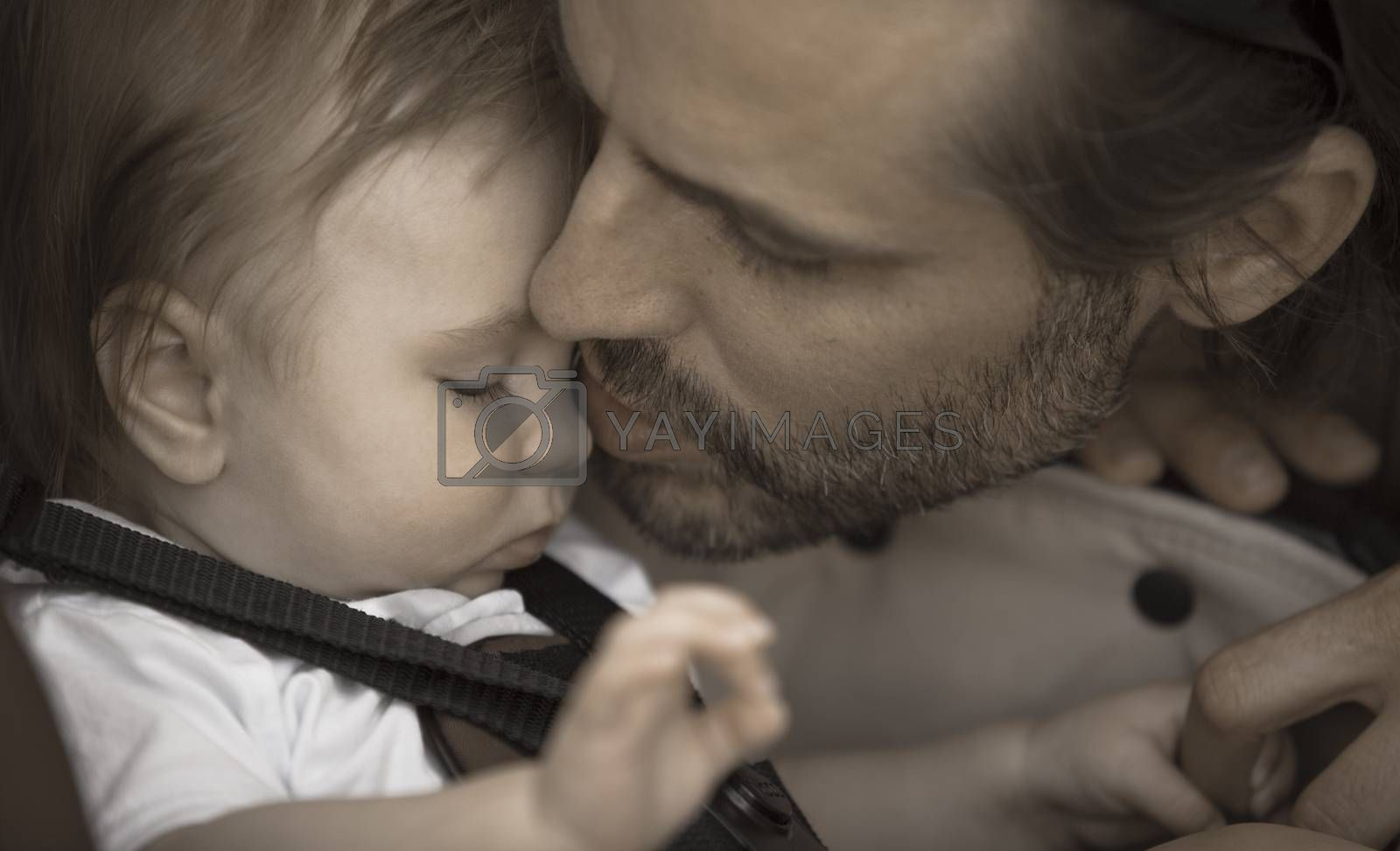 A father is kissing gently his young baby boy on the nose. Aged photo effect.
