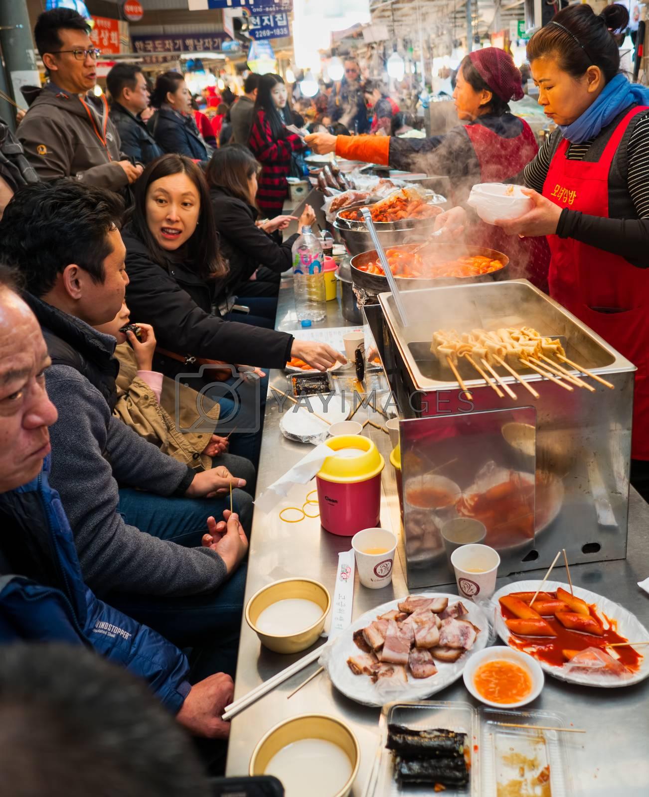 seoul, south korea - 11th november 2017: foodies pack the crowded traditional food street stalls at gwangjang market