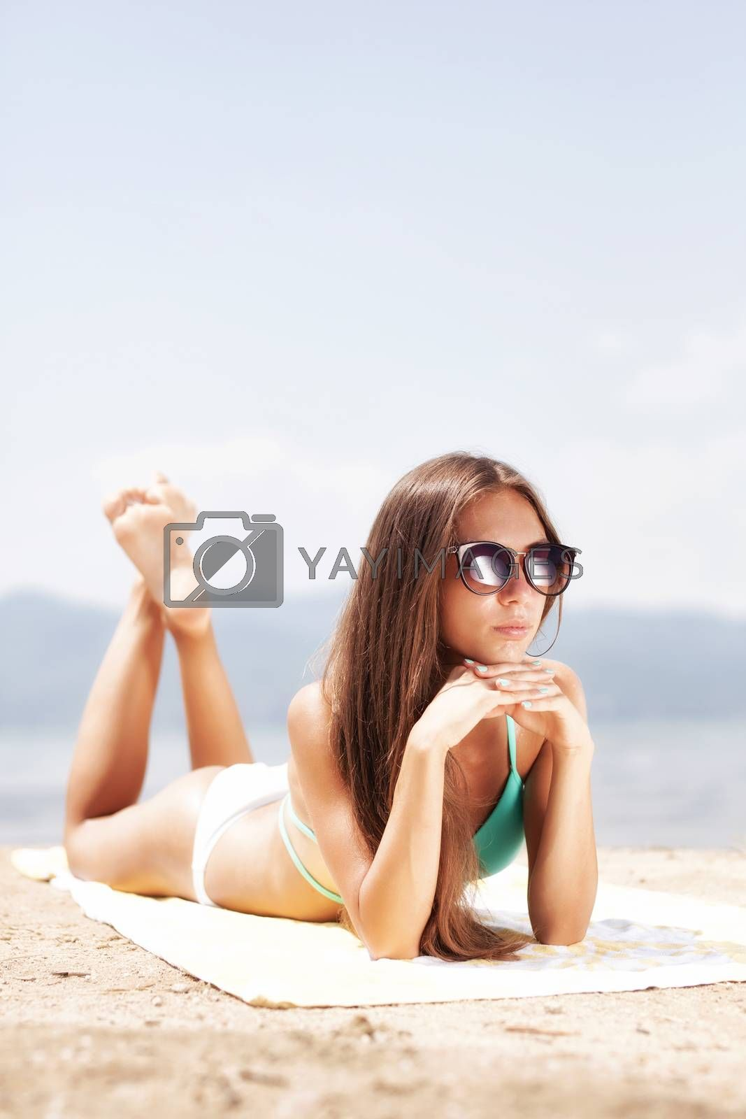 Royalty free image of girl sunbathing on a beach by kokimk