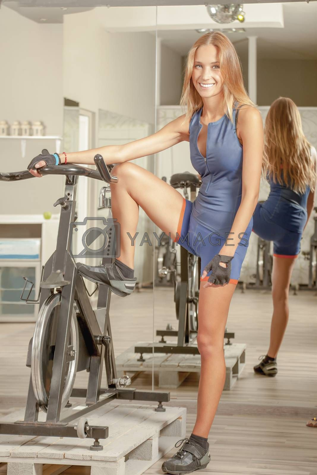 Royalty free image of Beautiful Young Woman Cycling Gym by vilevi