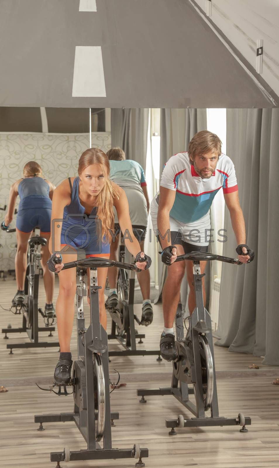 Royalty free image of Young Active People Gym Cycling by vilevi
