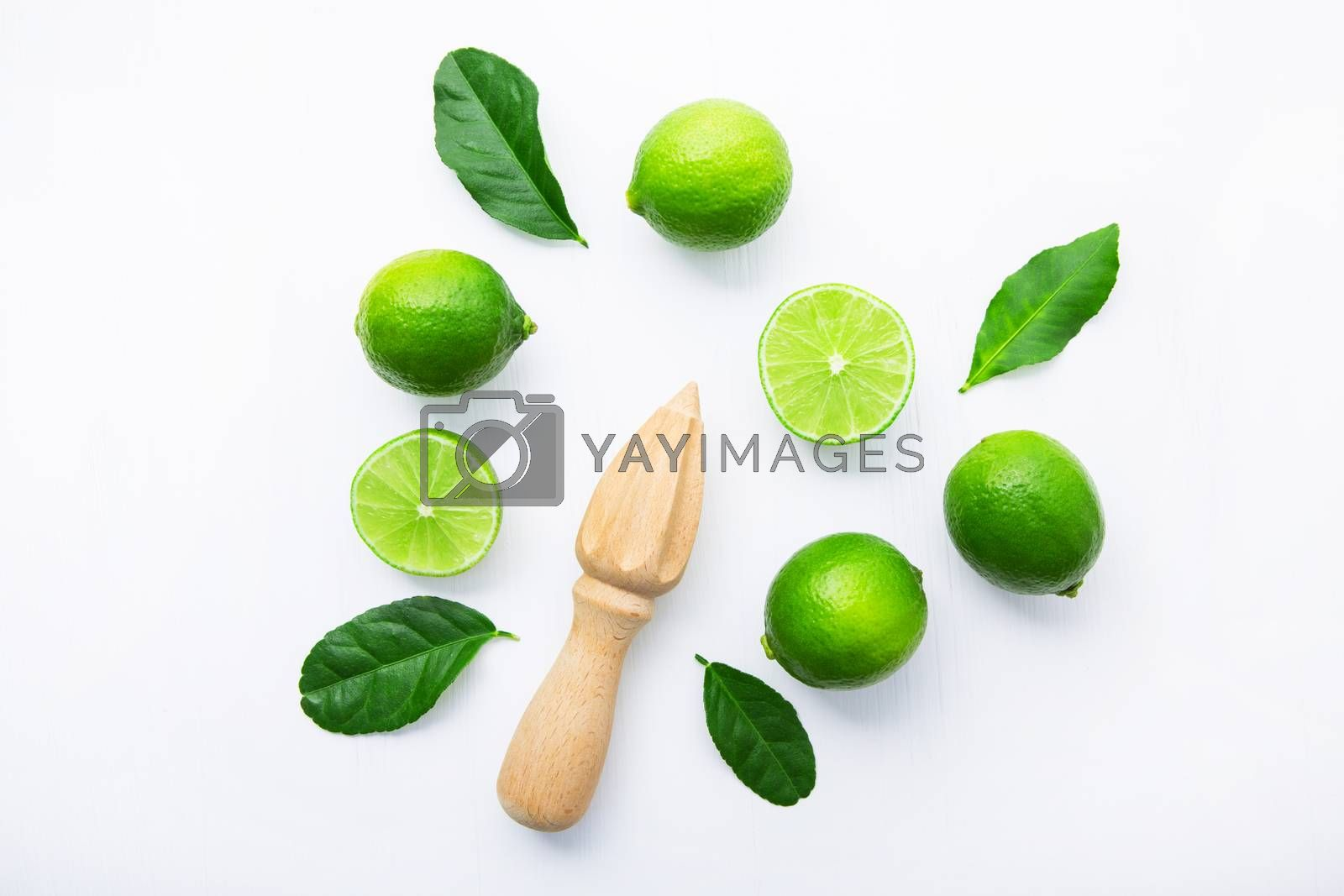 Fresh limes and wooden juicer on white background. Top view with by Bowonpat