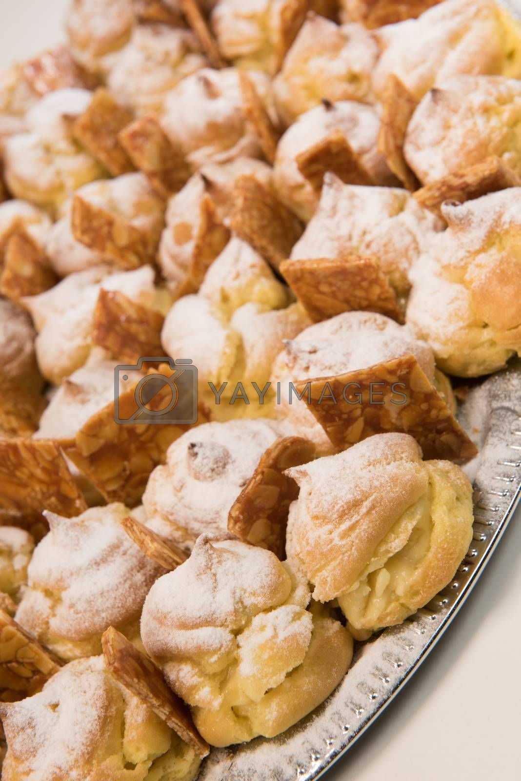 Cream puffs filled vanilla custard and dusted with icing on a plat and nougatine, France
