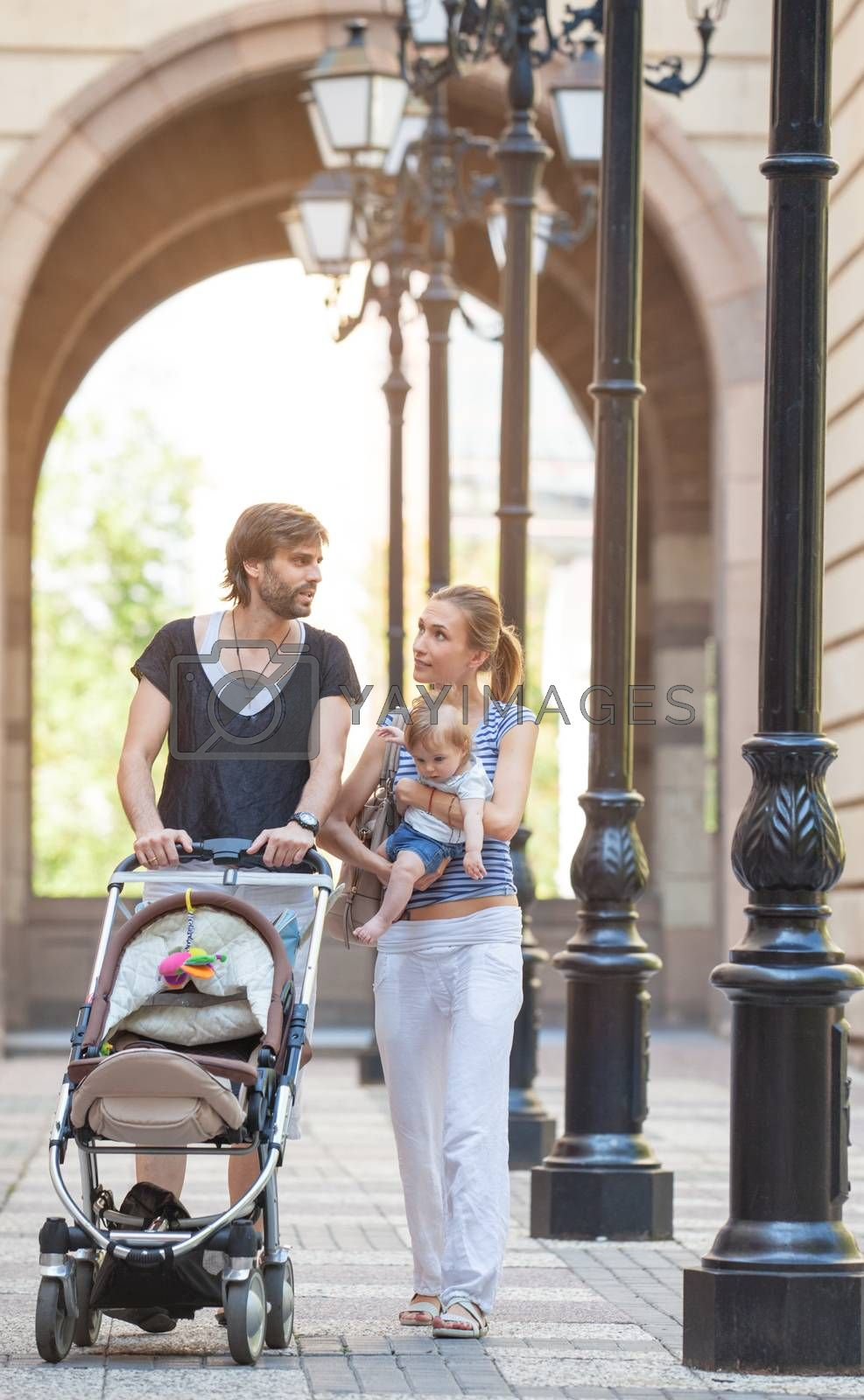 A young gorgeous couple is taking a walk in European city environment during summer time.