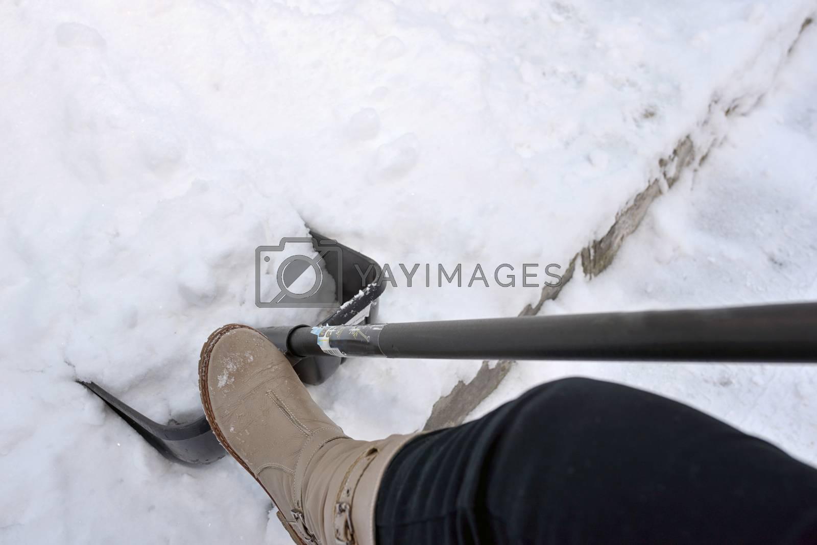 Woman Shoveling snow on street