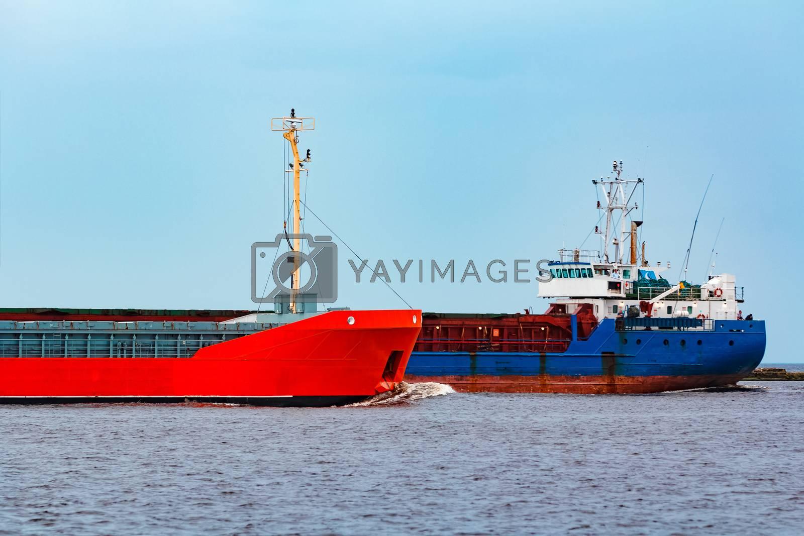 Orange cargo ship sailing past the blue bulk carrier