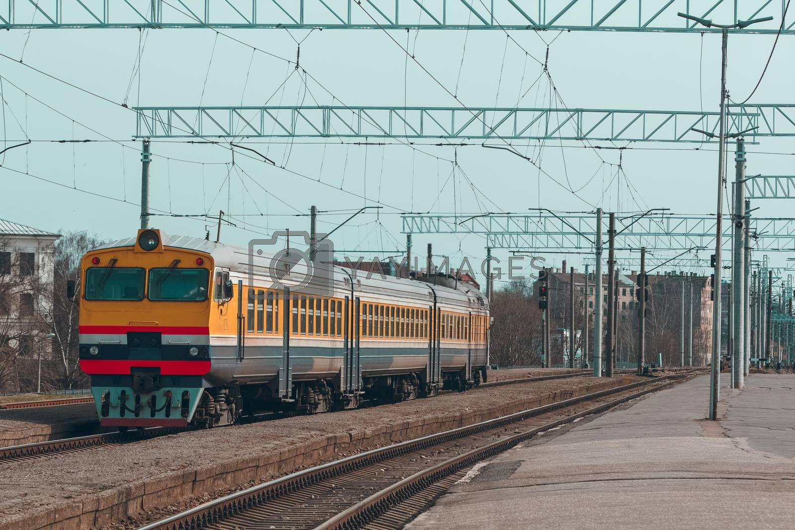 Old yellow passenger diesel train moving at the terminal