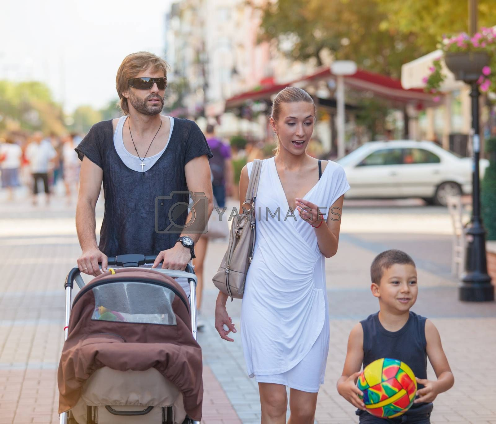 A family of four is taking time together with a walk downtown in a sunny summer day.