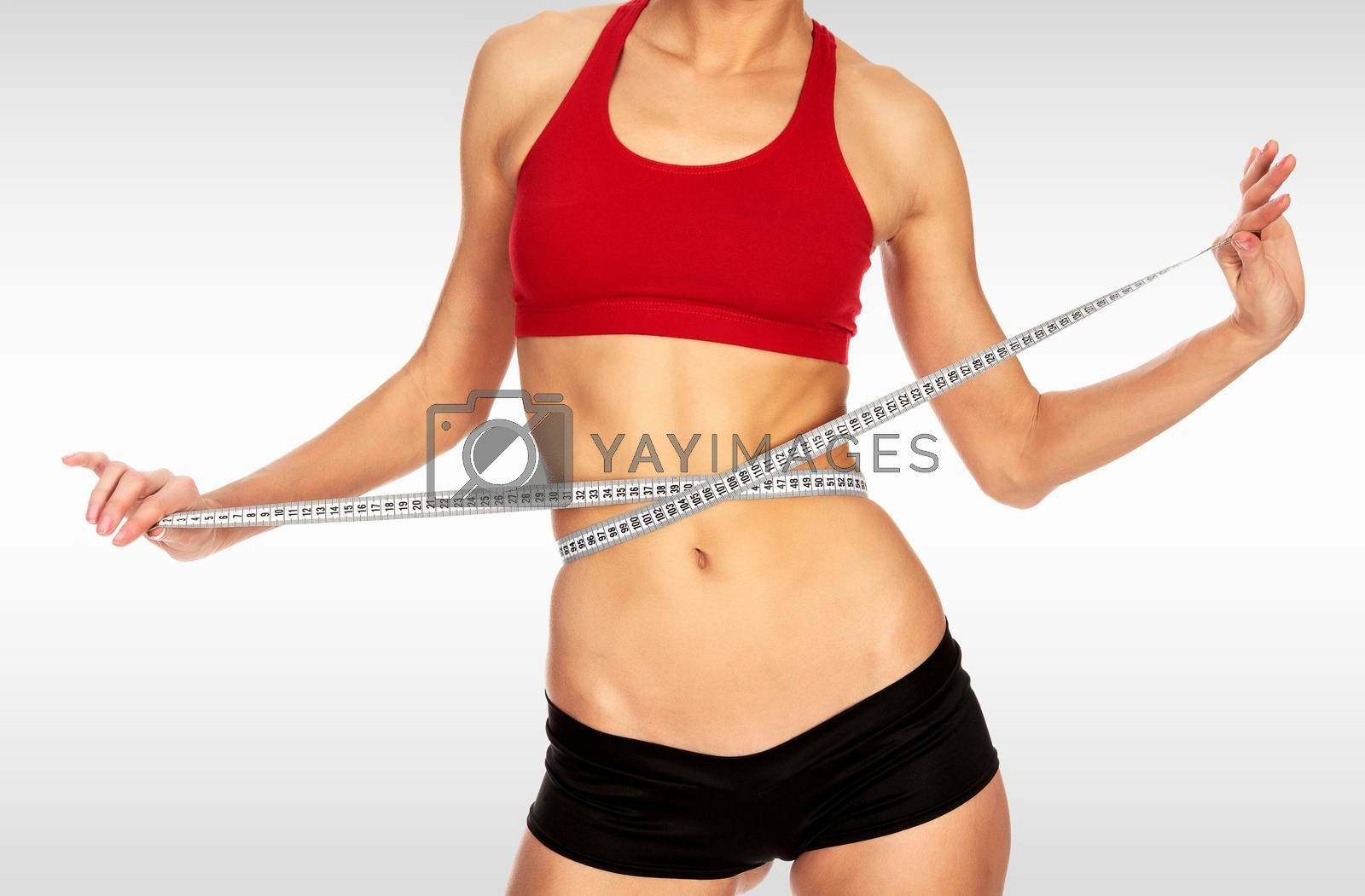 Fitness woman with a tape measure against a grey background with copyspace