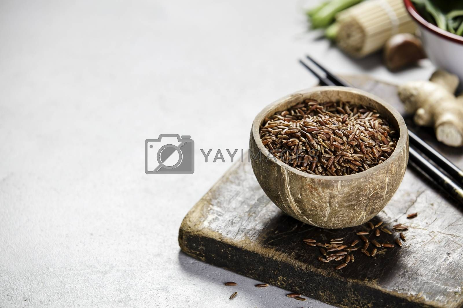 Asian food concept - rice in coconut shell on concrete background