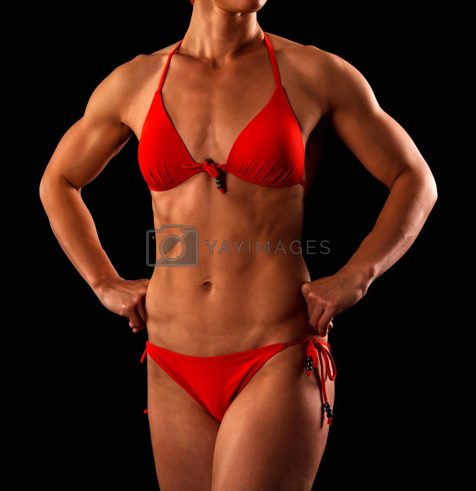 Sexy sports woman in red bikini posing against black background