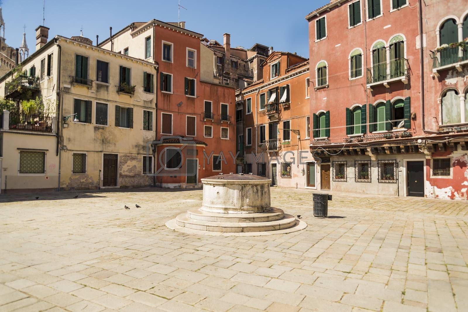 Old buildings and square with a well in Venice, Italy