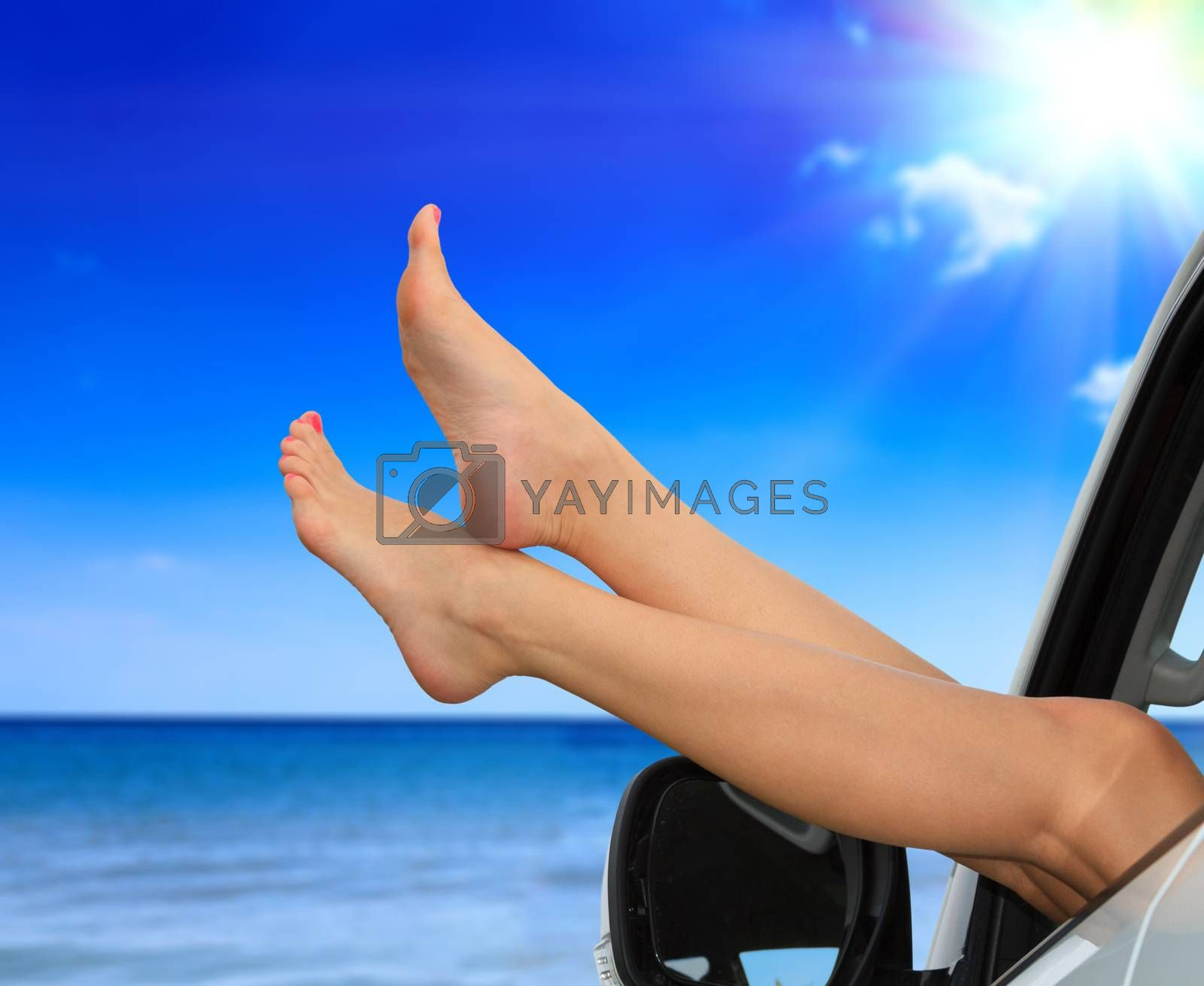 Beaitiful female legs against the sea and summer blue sky. Vacation, travel summer holidays concept. Woman shows her slim legs from the car window