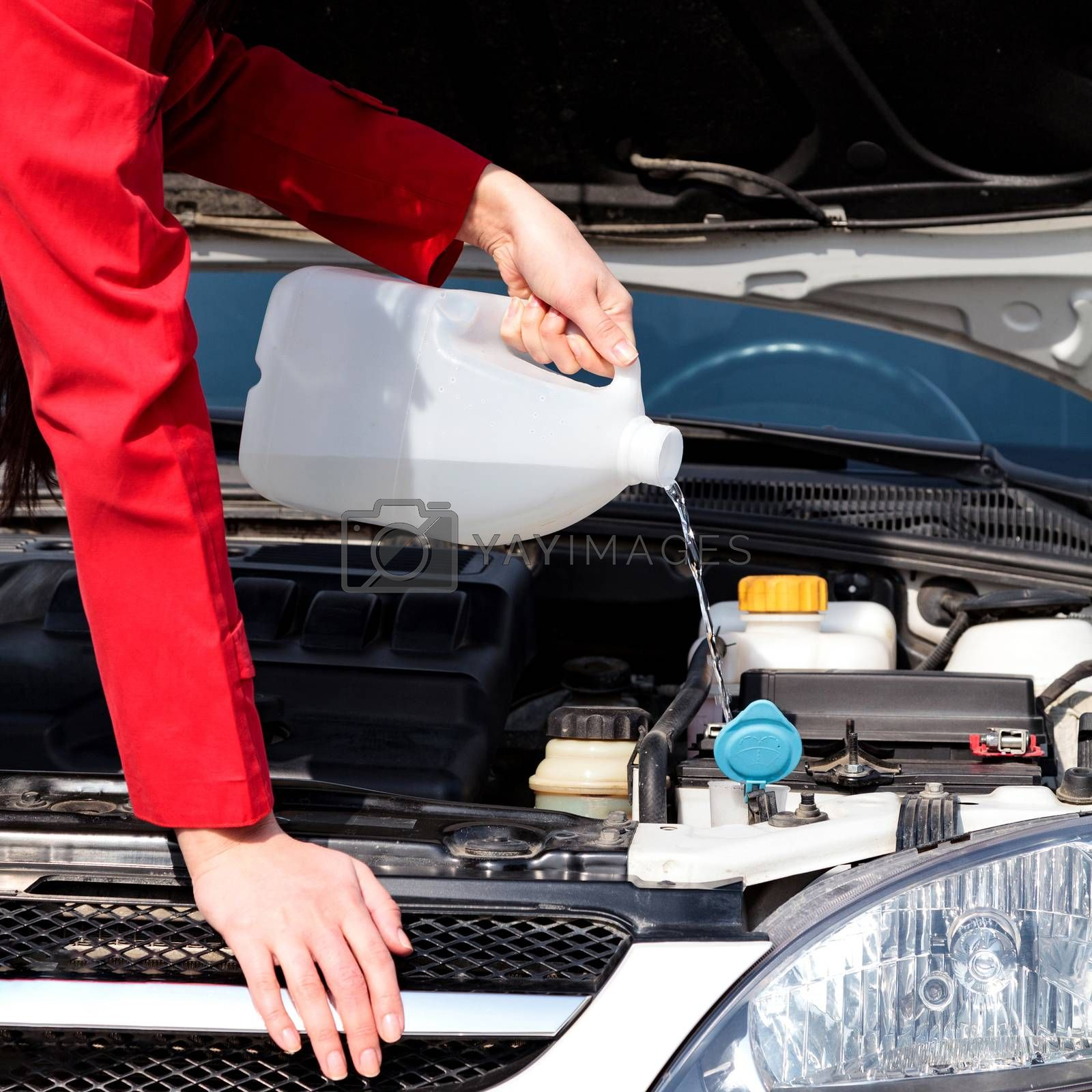 Cropped image of woman pouring windshield washer fluid into car