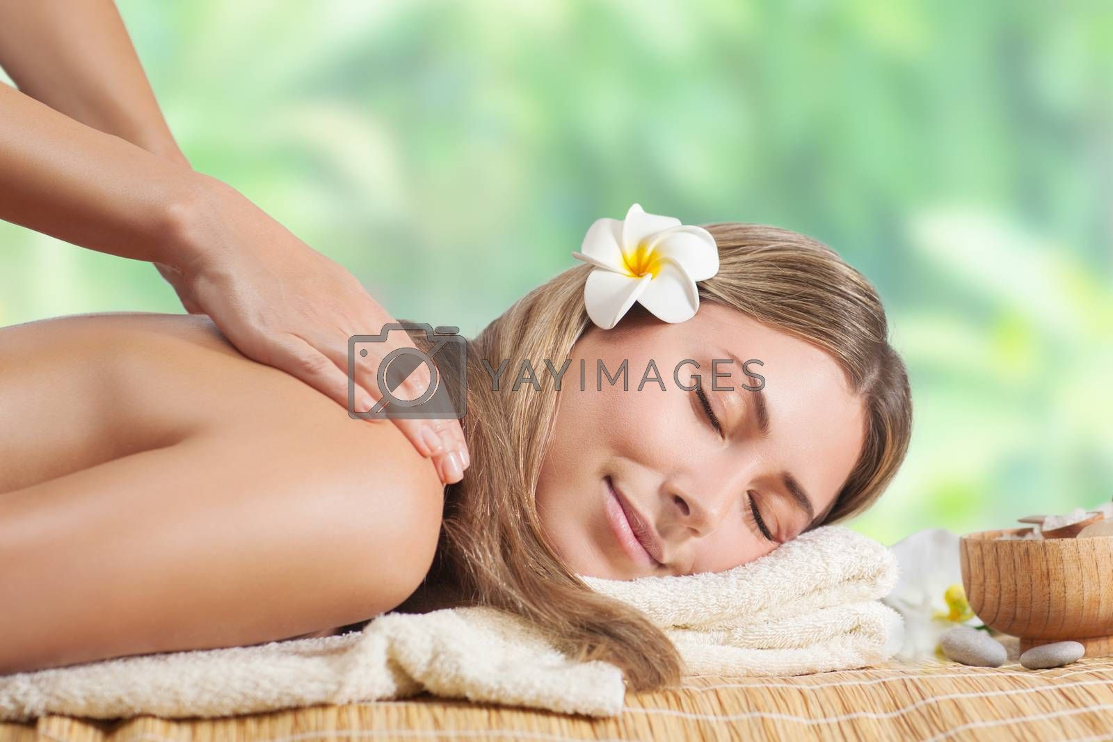 Beautiful girl enjoying day spa on the beach resort, lying down on the massage table and enjoying treatment procedure, health and beauty care concept