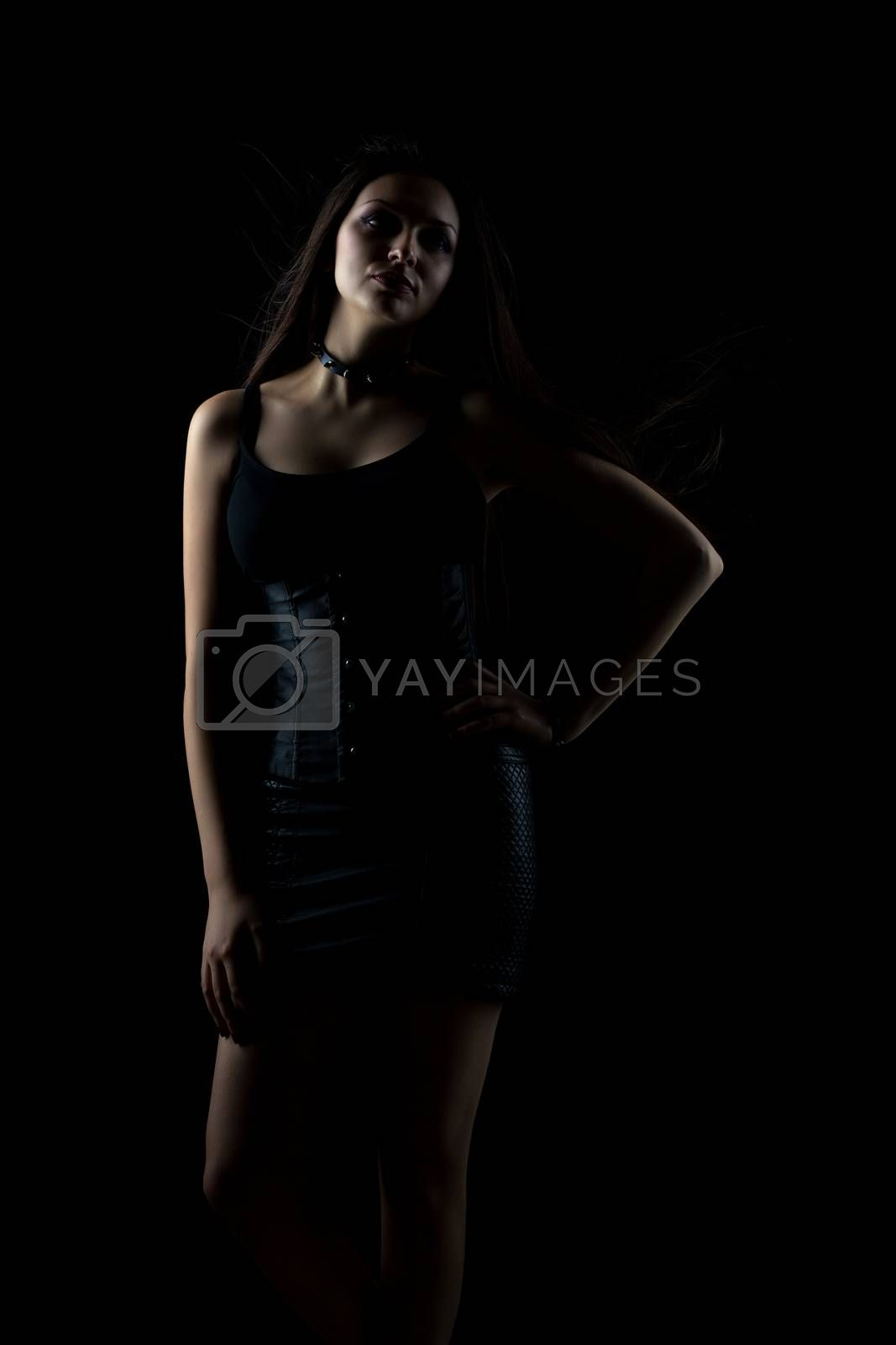 portrait of young sexy girl with long hair on dark background in studio, goth style