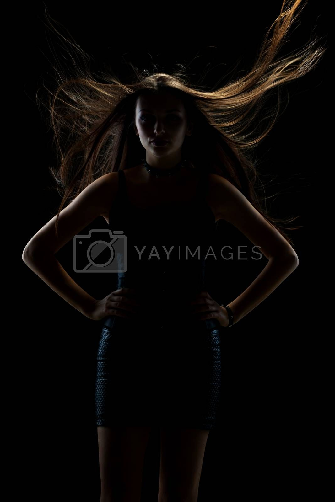 portrait of young sexy girl with long hair in the air on dark background in studio, goth style