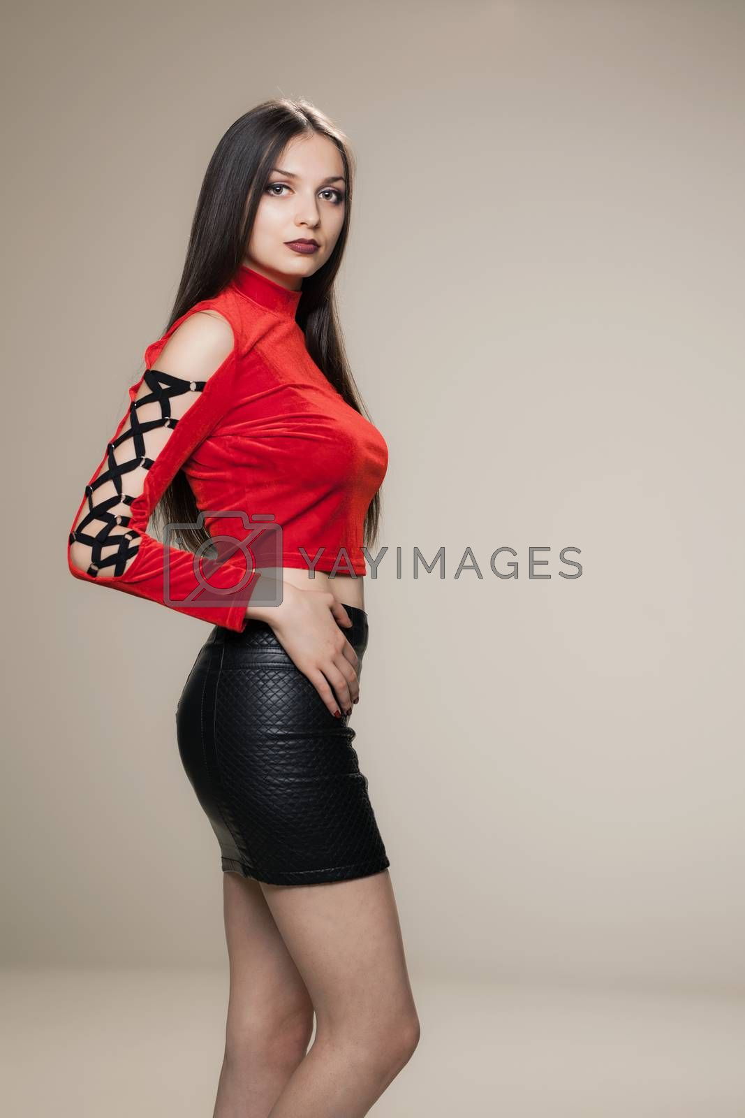 gothic style girl posing in studio wearing a red shirt and black short dress