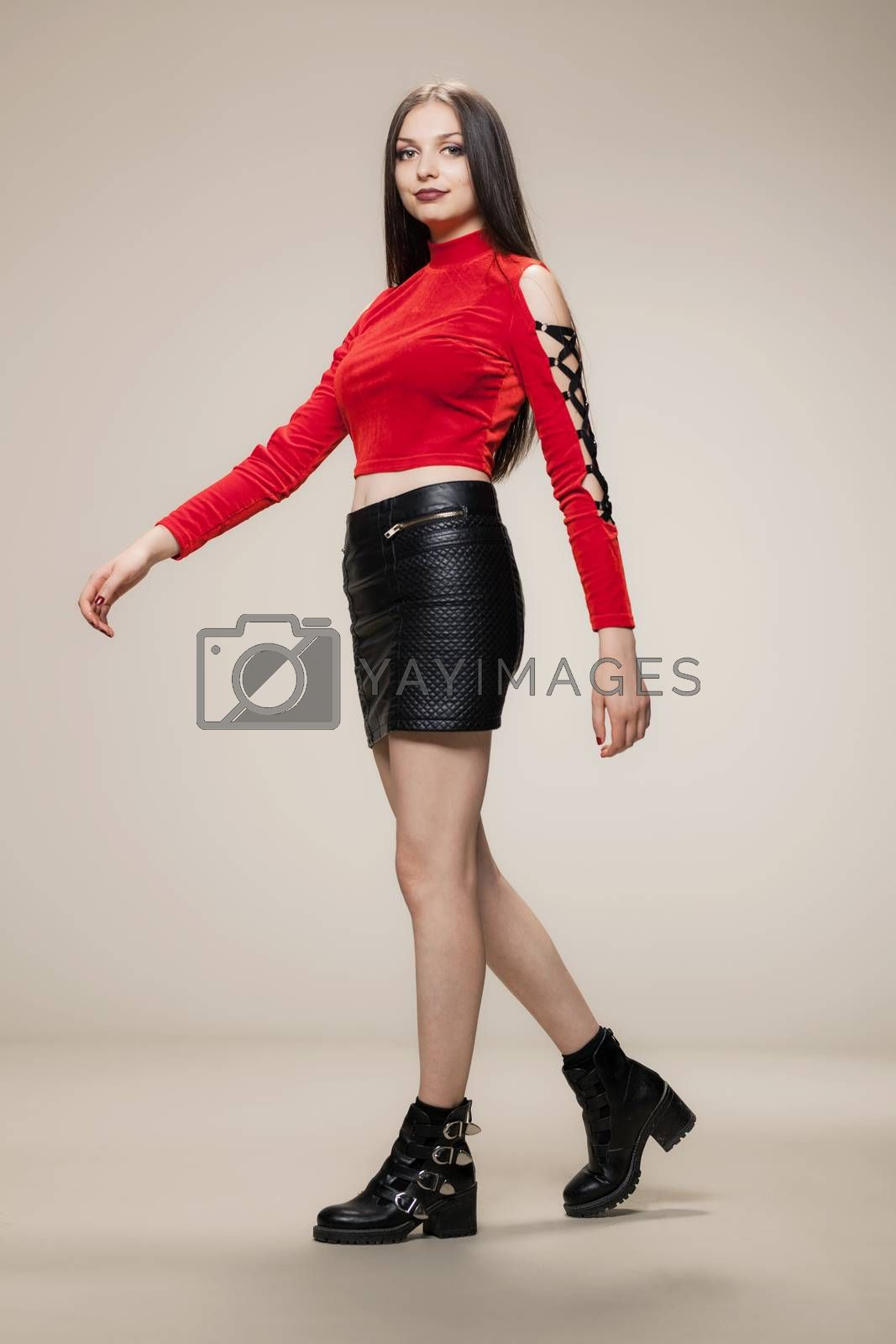 girl in red shirt, short black dress and boots, walking