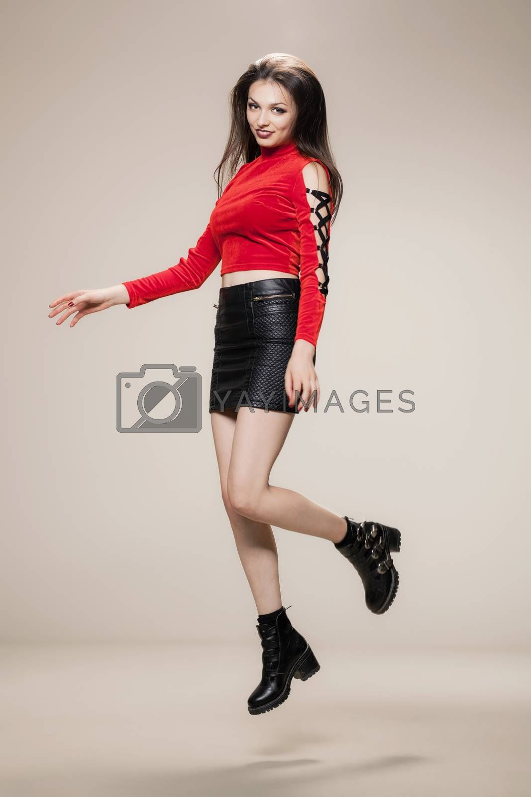jumping girl in red shirt, short black dress and boots