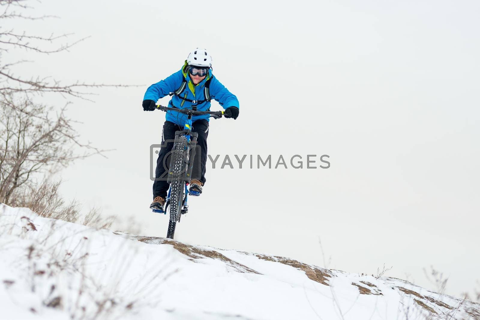 Cyclist in Blue Riding Mountain Bike on Rocky Winter Hill Covered with Snow. Extreme Sport and Enduro Biking Concept. by maxpro