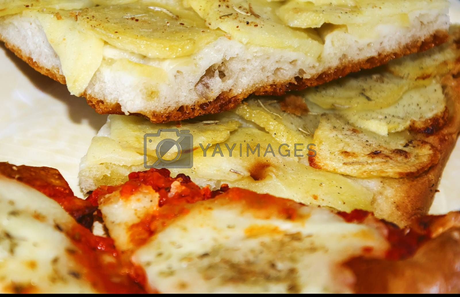 close up of two slices of pizza with tomato, mozzarella and potatoes