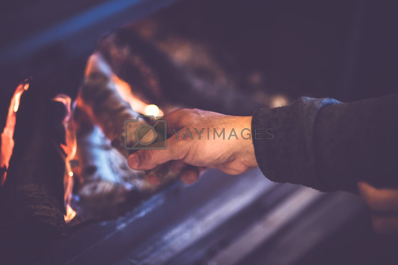 Man kindles a fireplace, closeup photo of a men's hand throws firewood into the fire, romantic winter time evening near fireside in the country house