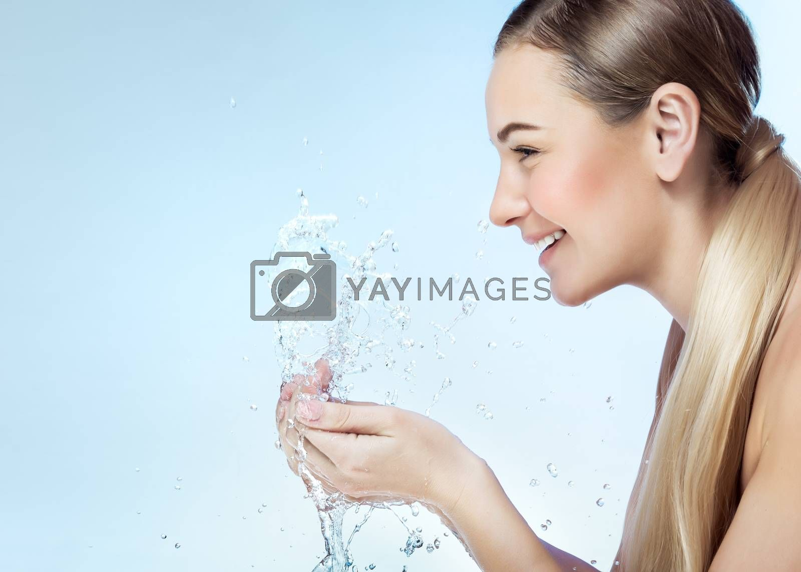 Profile portrait of a nice blond girl with pleasure washing her face in the morning by clear refreshing water, perfect clean skin, using anti acne remedy, photo with a copy space