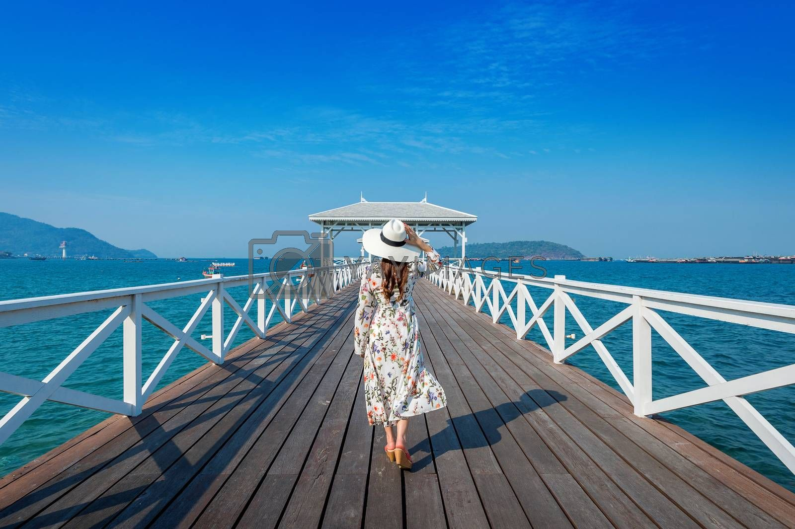 Young woman walking on wooden bridge in Si chang island, Thailand.