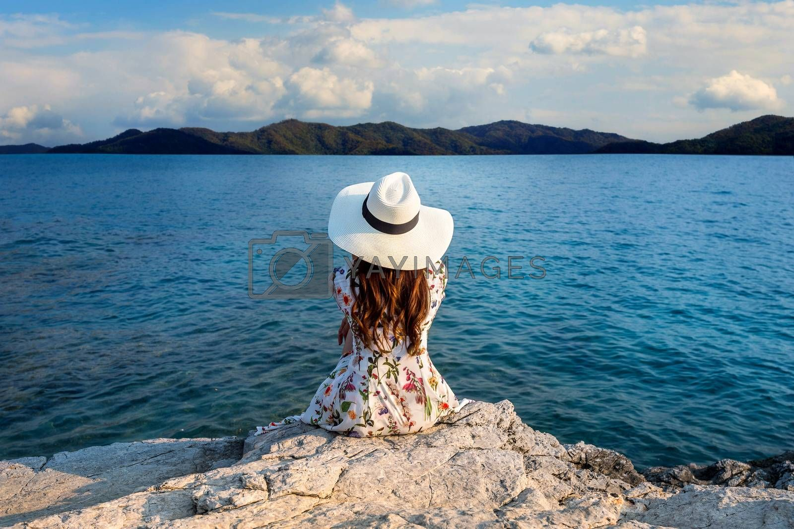 Young woman sitting on the top of rock and looking at the seashore.