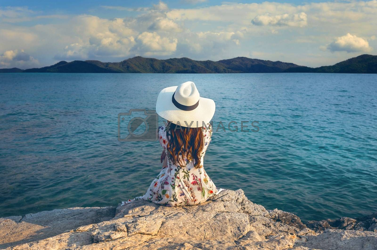 Young woman sitting on the top of rock and looking at the seashore. Vintage tone.