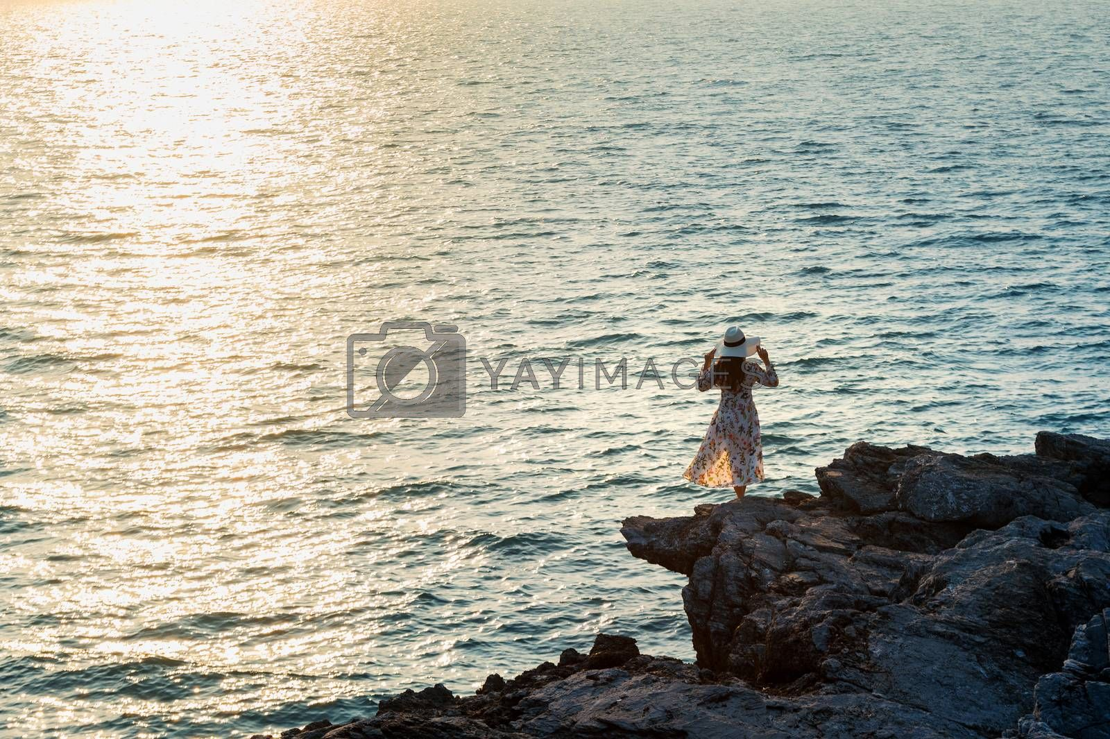 Young woman standing on the top of rock and looking at the seashore and sunset in Si chang island.