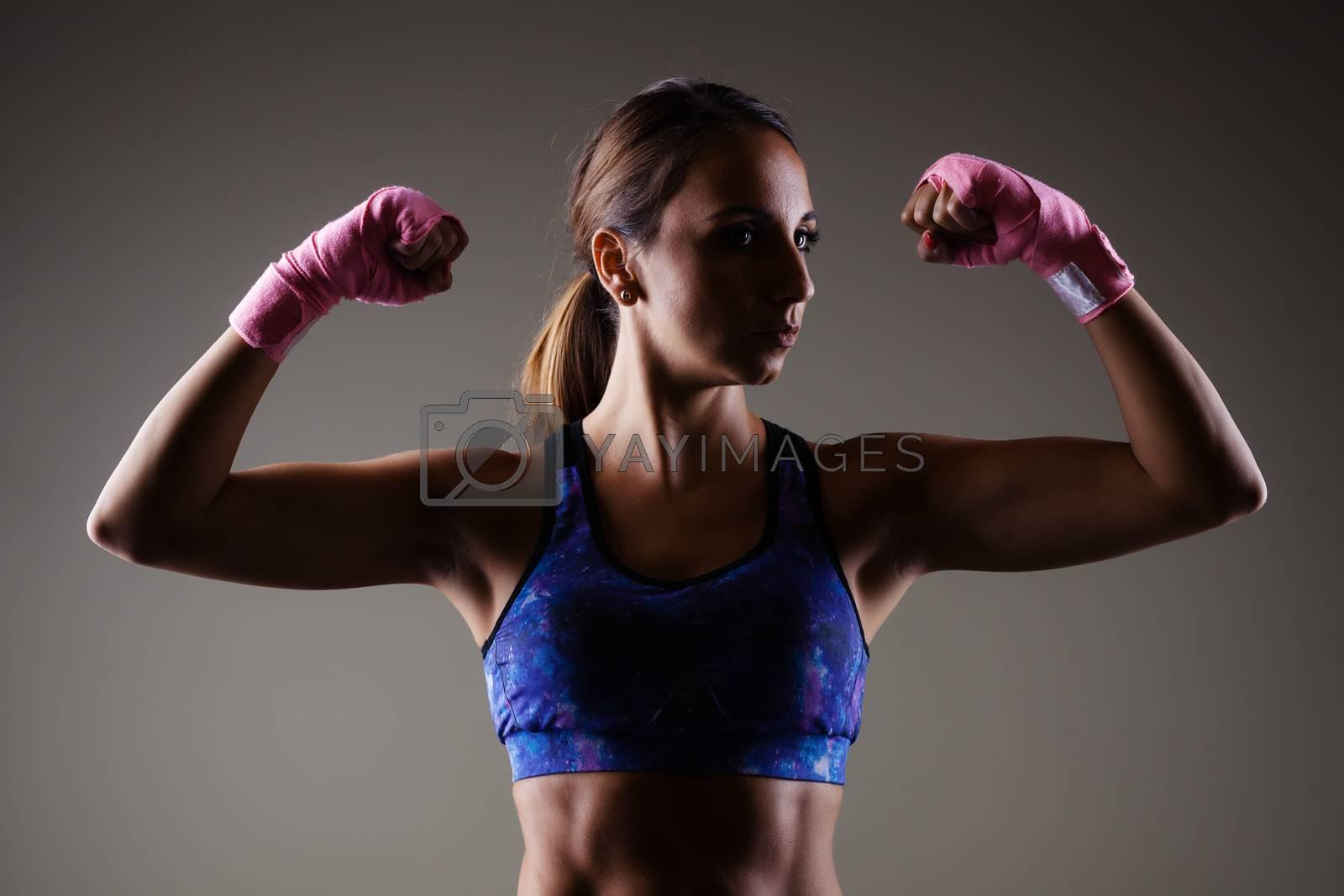 girl kickboxer posing with pink hand wraps