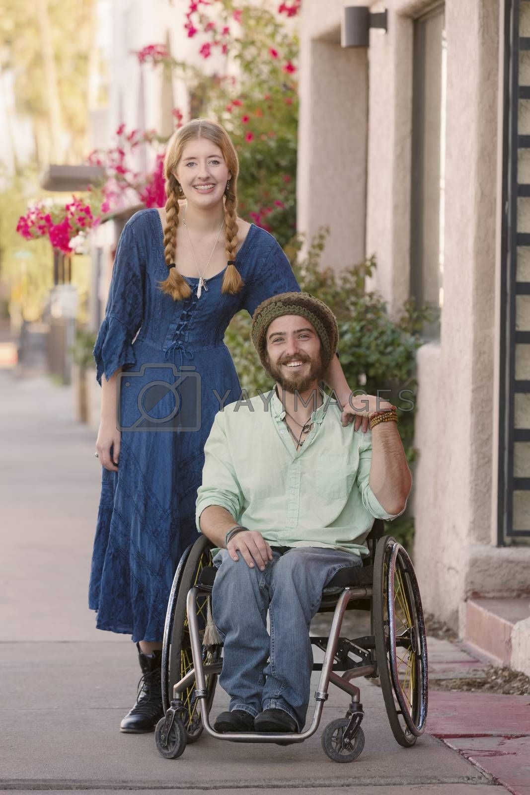 Woman with male friend in wheelchair on sidewalk