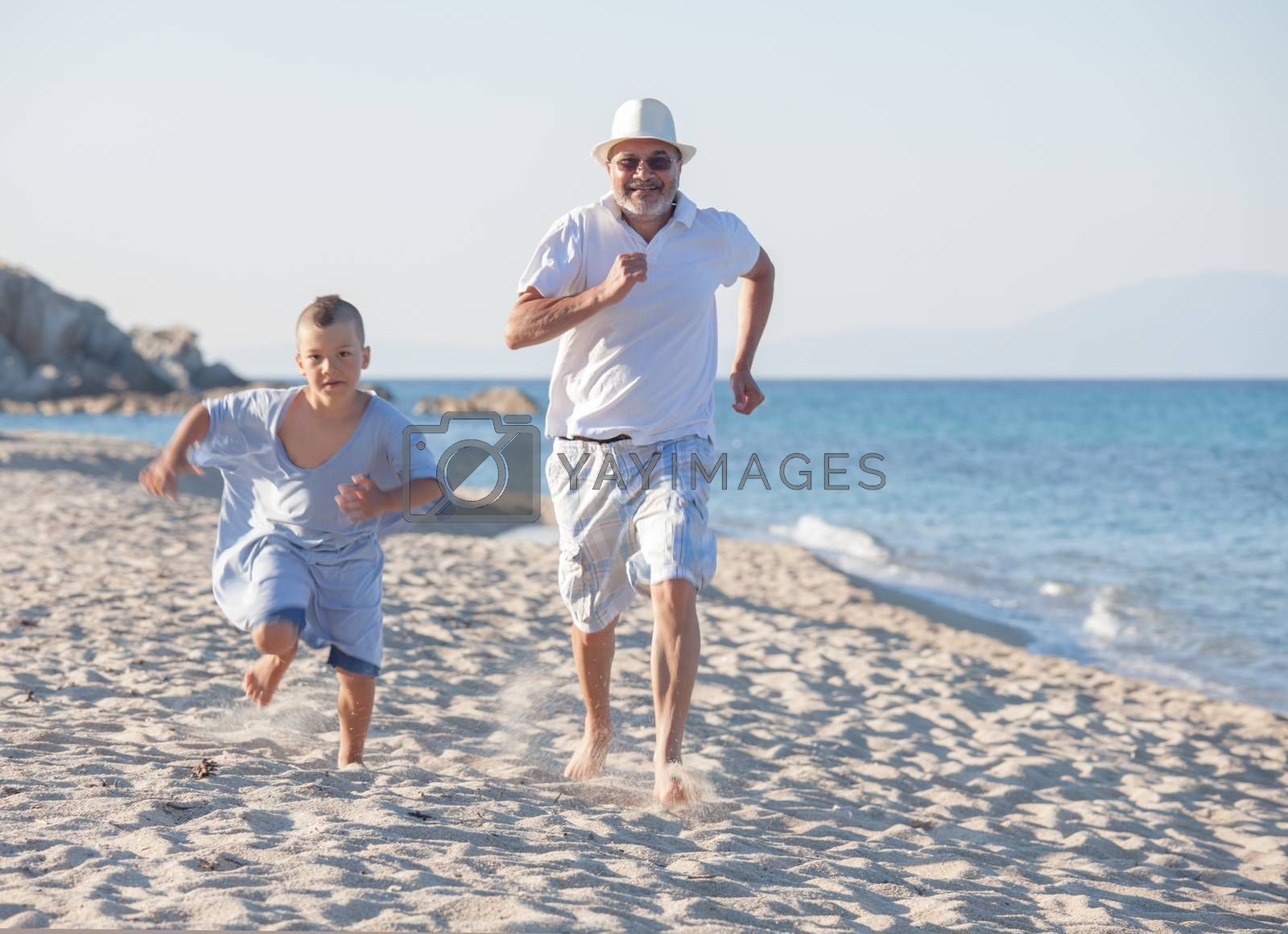 Royalty free image of Competition Beach Sea Grandfather Generations Grandson Running by vilevi