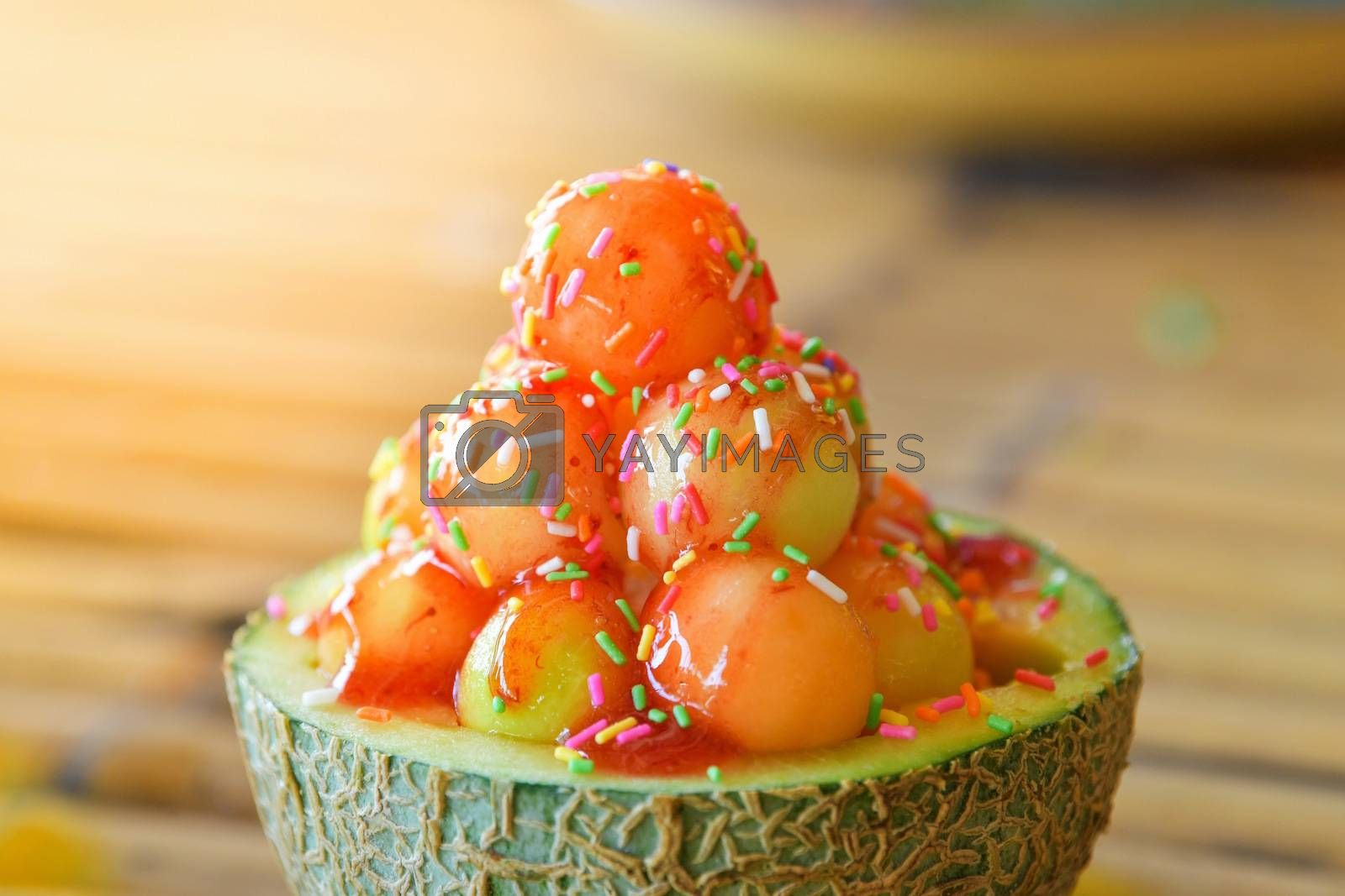 Ice cream cantaloupe with topping in cantaloupe.
