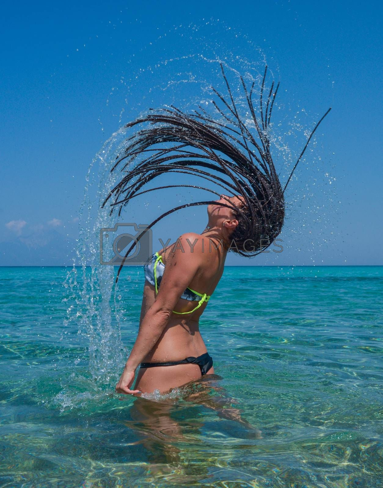Beautiful girl splashing water with her hair in the sea or ocean.