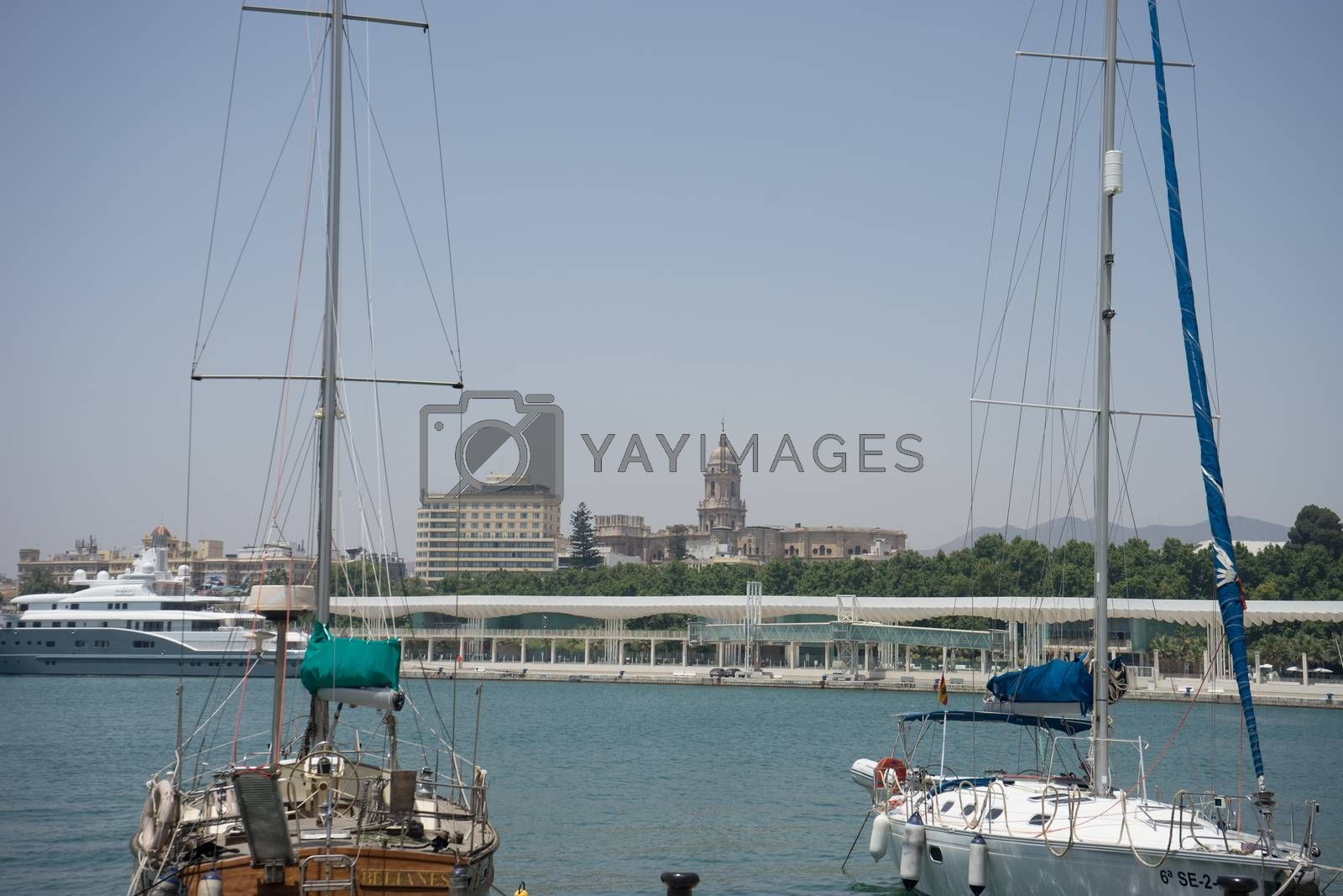 Boats with their sails down docking at the harbour in Malaga, Spain, Europe on a summer day with clear skies