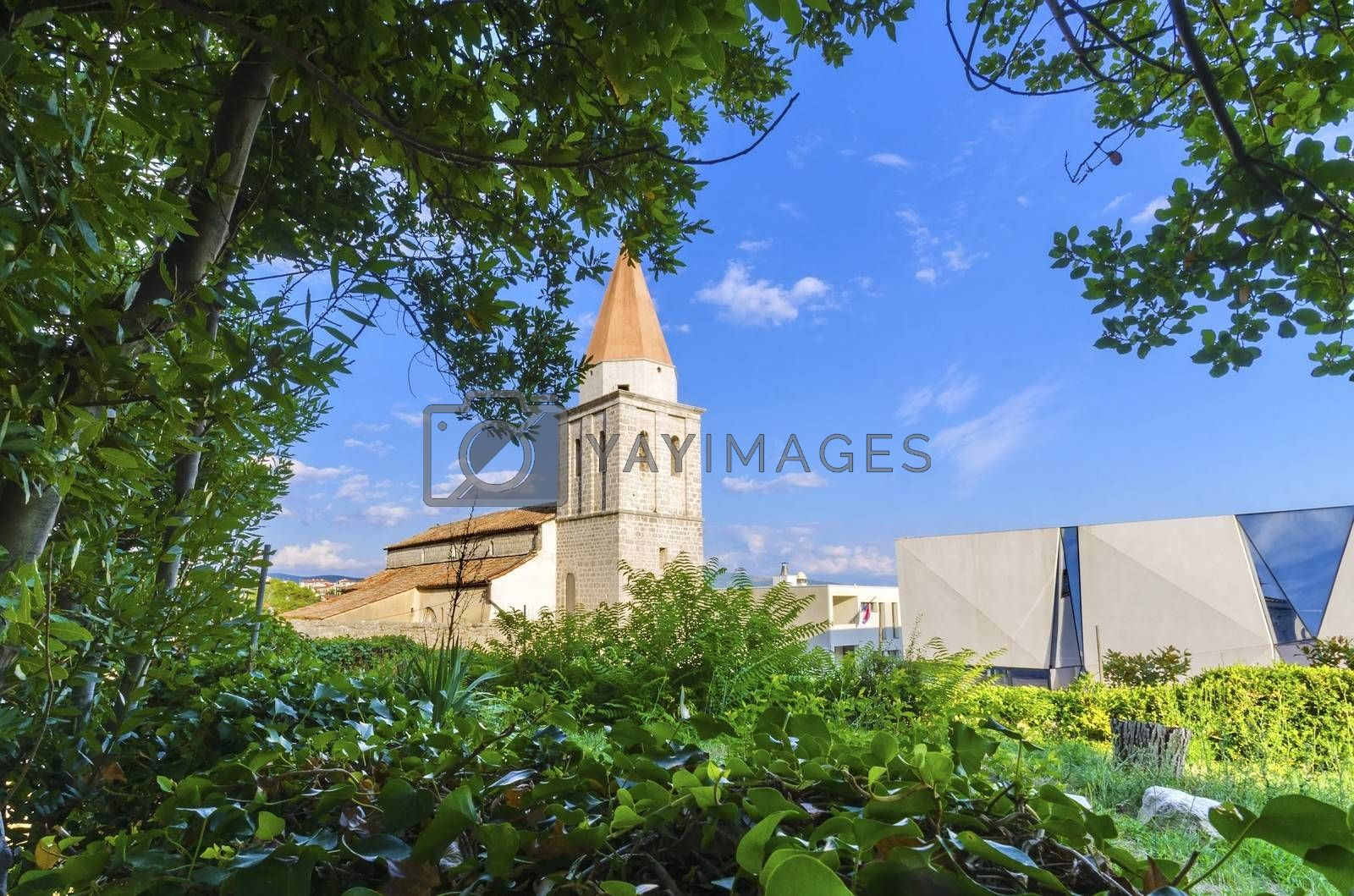 The pyramidal tower of the Church of our Lady of Health, a romanesque cathedral formerly named St Michael the archangel, basilica at the Square of the The Glagolitic housed monasteries on Krk island, in Croatia and the elementary school mirrors.