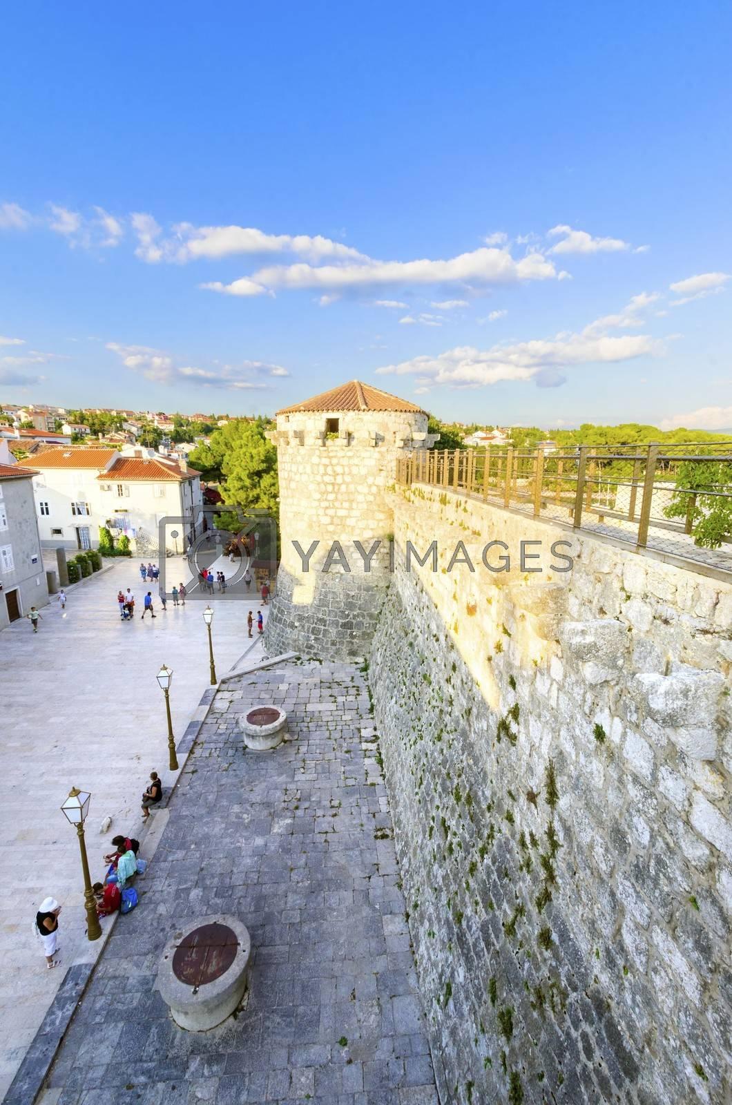 The round venetian tower of Frankopan Castle and the Kamplin square in Krk, Croatia - Frankopanski Kastel, part of the medieval city walls and now promenade.