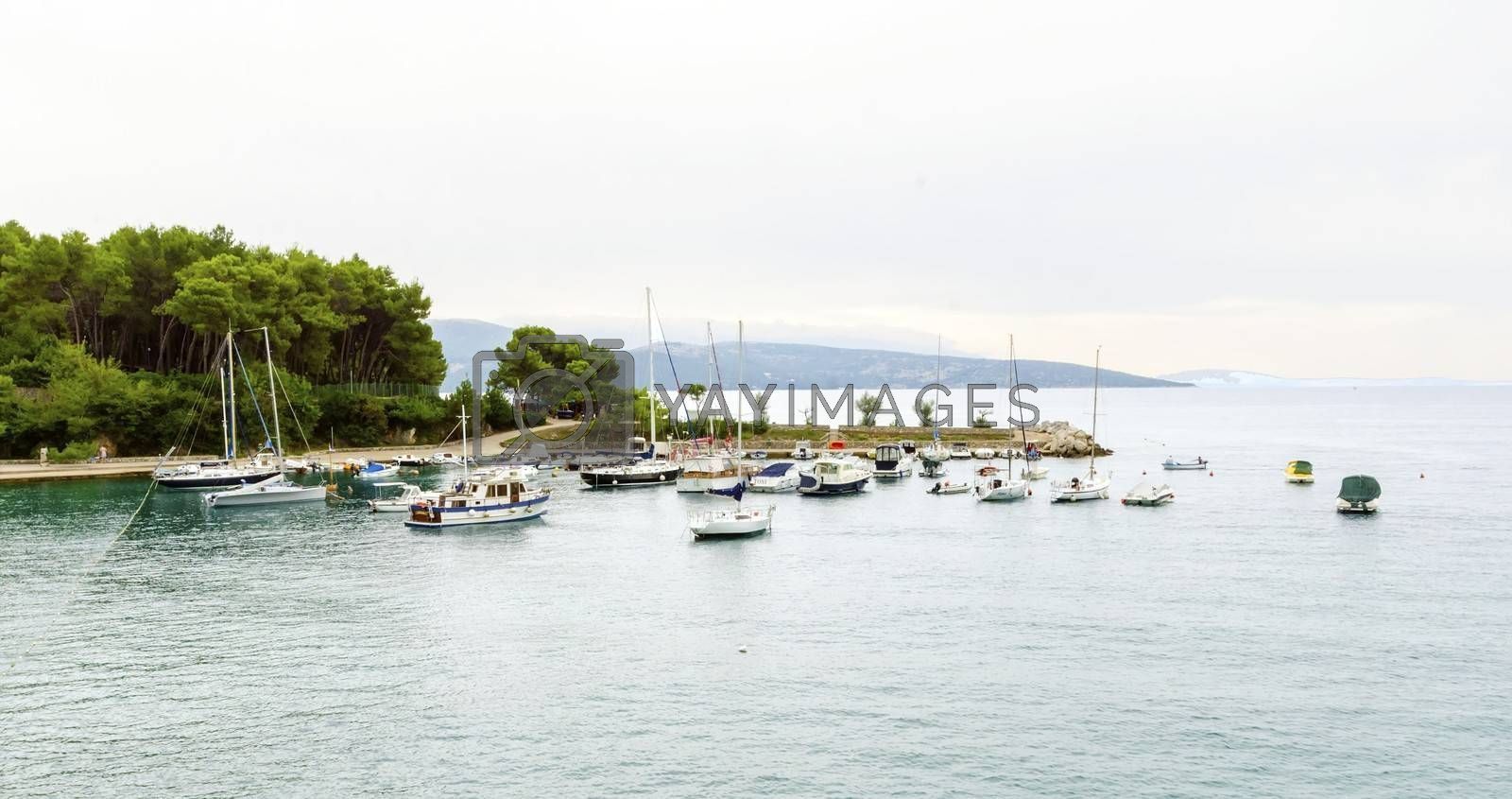 The port on the old town of Krk in Croatia, county Primorje-Gorski Kotar. A view of the Adriatic sea, boats docked, the coast of the island Veglia and part of the city walls.