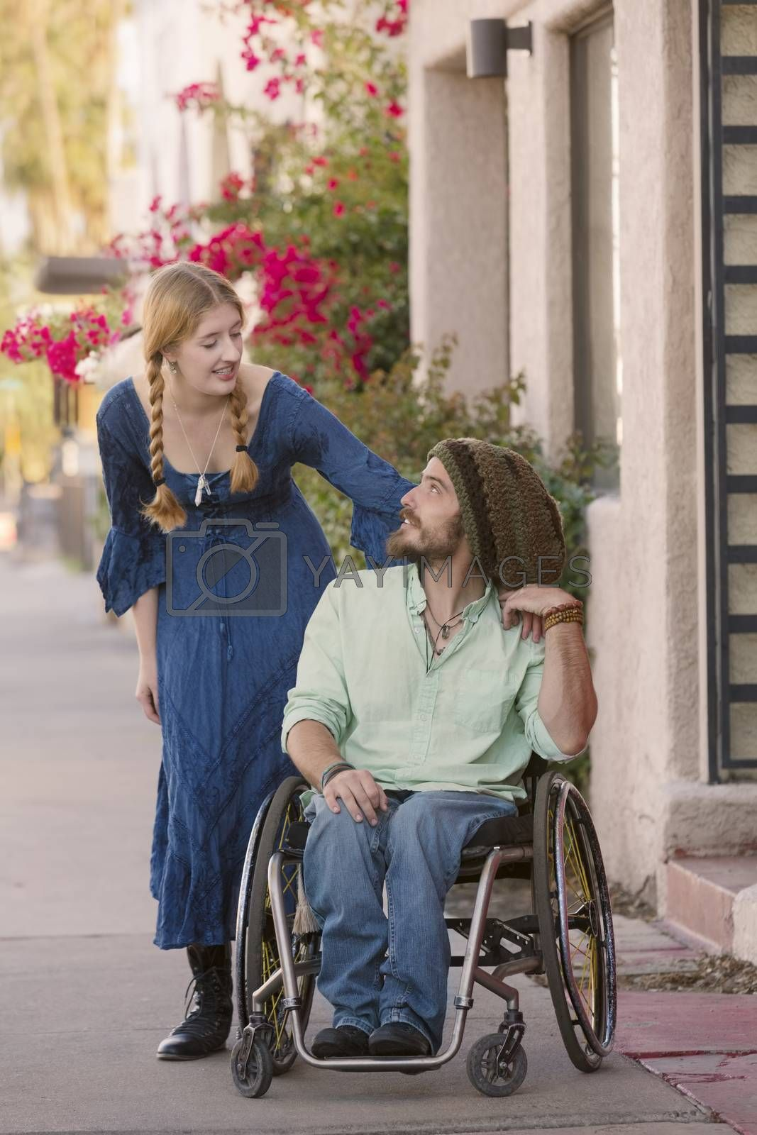 Woman talking with friend in wheelchair on sidewalk
