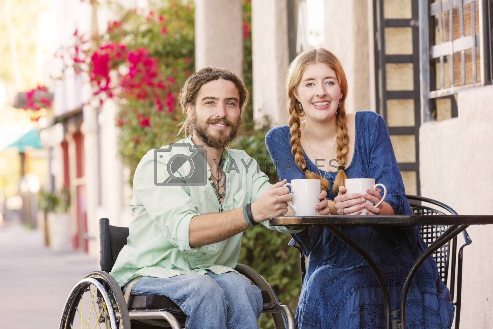 Woman having coffee with male friend in wheelchair at outdoor cafe