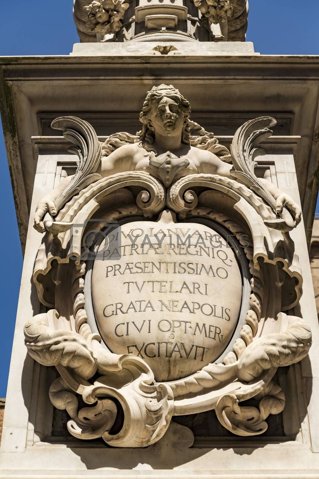 Ancient obelisk of San Gennaro in Naples in barocco hat houses an oval with the inscription of dedication to the saint, enclosed in a frame embraced by a statue of the siren .