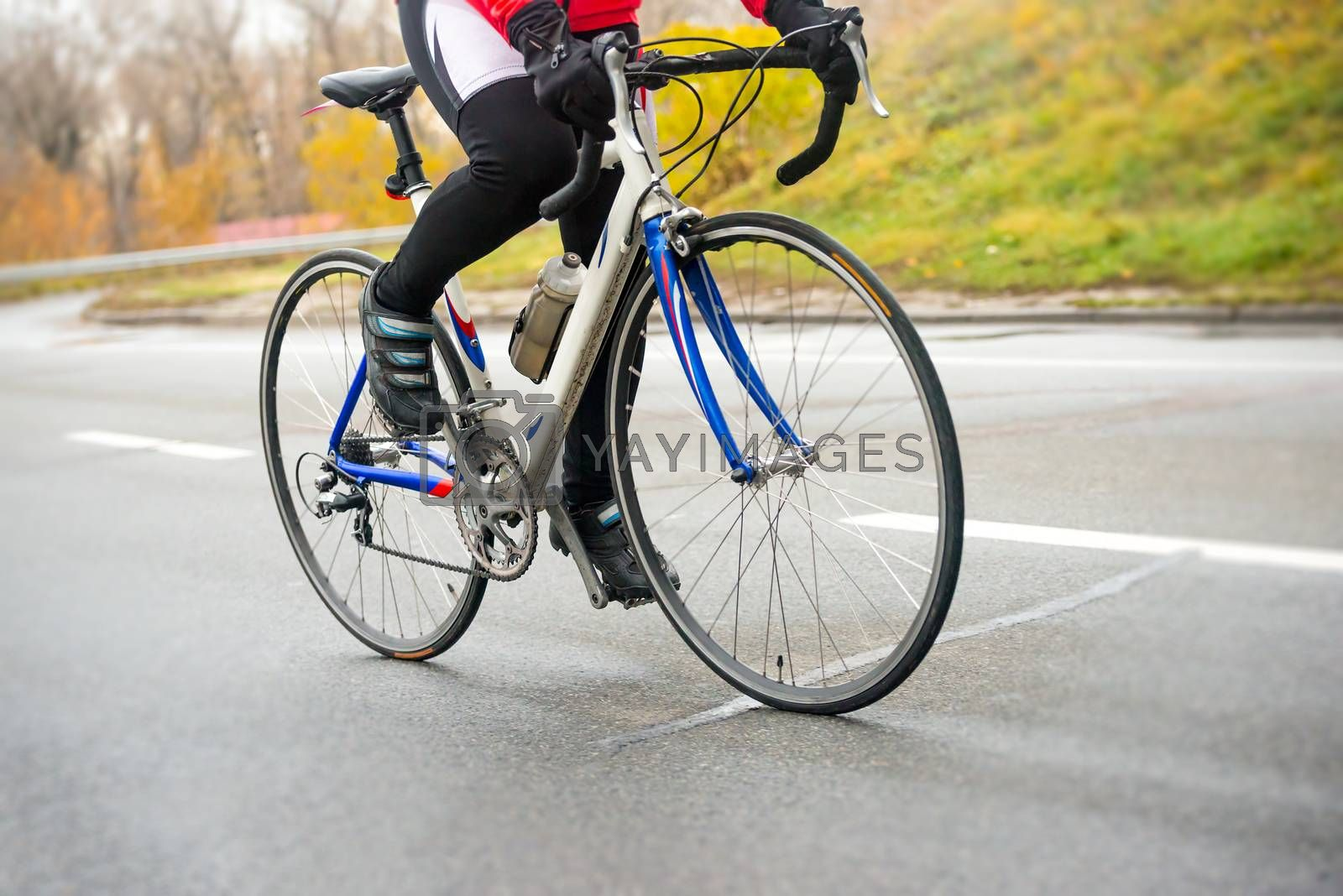 Young Woman Riding Road Bicycle on the Highway in the Cold Autumn Day. Healthy Lifestyle Concept.