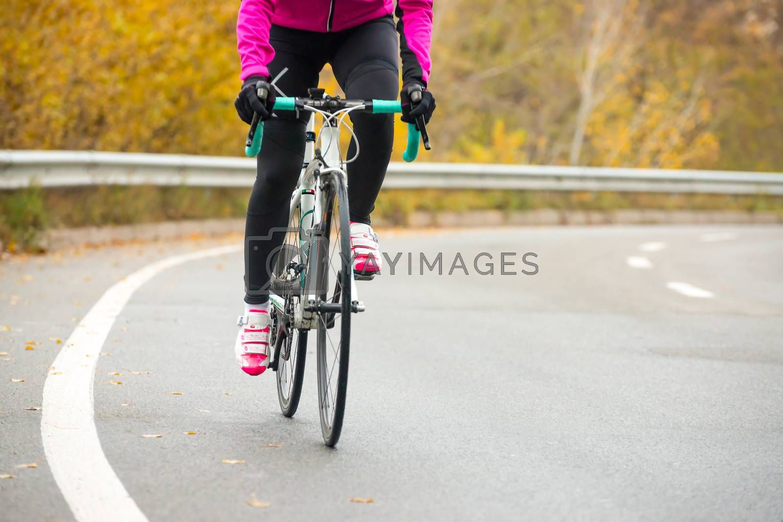 Young Woman in Pink Jacket Riding Road Bicycle on the Highway in the Cold Autumn Day. Healthy Lifestyle. by maxpro