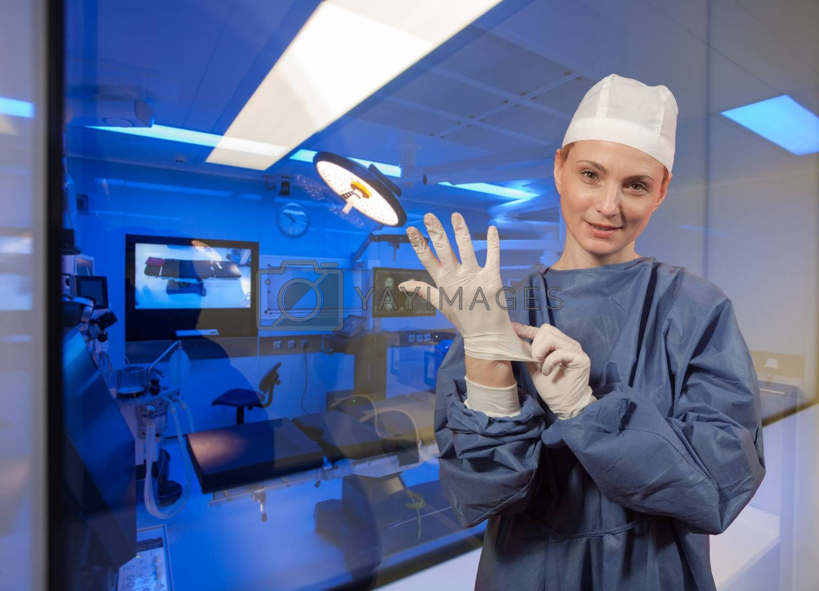 A medical personal putting protective surgeons glove in front of operating room.